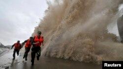 Para tentara berlari saat gelombang besar yang dipicu oleh topan Fitow menghantam garis pantai di Wenling, provinsi Zhejiang (6/10).