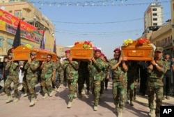 "FILE - Members of the Shi'ite group Asaib Ahl al-Haq, or ""League of the Righteous,"" carry coffins of colleagues killed while helping Iraqi security forces battle Islamic State group in Beiji, at a funeral in Najaf, 160 kilometers south of Baghdad, Oct. 18, 2015."