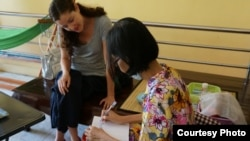 Erin Harrelson is having a conversation using handwriting with a deaf sister of Mr. Youk Chhang at her house. (Photo provided by Erin Harrelson)