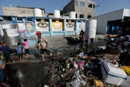 A U.N. worker cleans the garbage at the courtyard of the Abu Hussein U.N. school at Jebaliya refugee camp, northern Gaza Strip, July 30, 2014.
