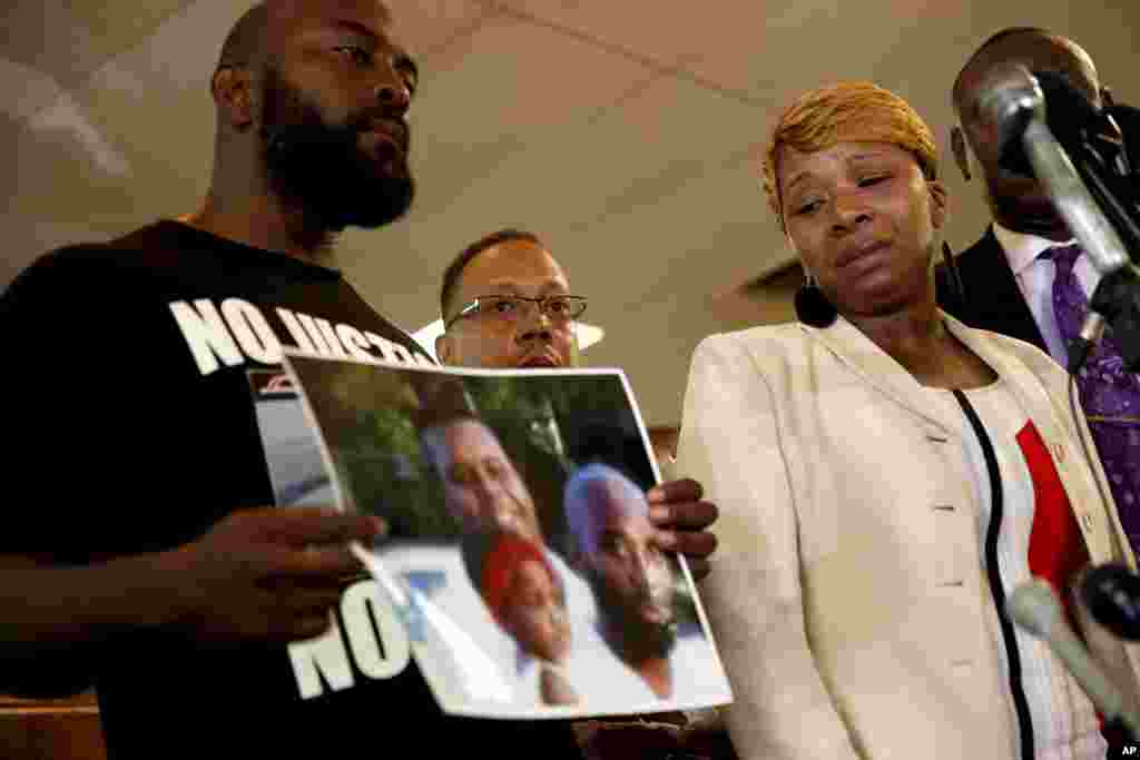 Lesley McSpadden (à direita), mãe do jovem de 18 anos, Michael Brown, ao lado do pai, Michael Brown, que segura uma fotografia de família durante a conferência de imprensa, Ago. 11, 2014.