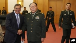 U.S. Defense Secretary Leon Panetta, left, and Chinese Defense Minister Liang Guanglie shake hands before their delegations meet at the Bayi Building in Beijing, China, September 18, 2012.