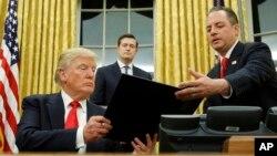 "Donald Trump menandatangani keputusan pertamanya melawan undang-undang asuransi kesehatan ""Obamacare""."