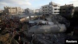 팔레스타인 자치령인 가자지구에서 9일 이스라엘군의 공습이 있은 후 팔레스타인인들이 무너진 건물 잔해 주위에 모여있다.
