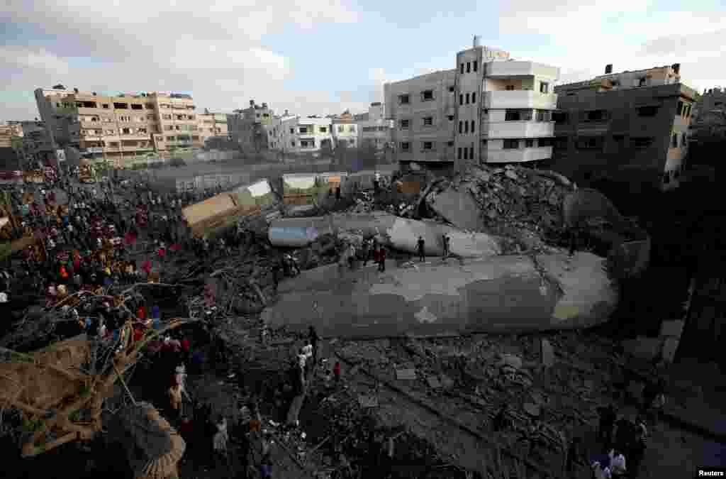 팔레스타인 자치령인 가자지구에서 이스라엘군의 공습이 있은 후 팔레스타인인들이 무너진 건물 잔해 주위에 모여있다. 팔레스타인 가자지구에서 이틀 동안 교전을 벌인 이스라엘과 무장 정파 하마스가 휴전에 합의한 것으로 알려졌다.