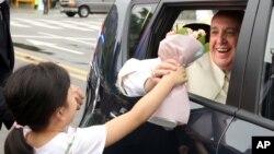 Paus Fransiskus menerima bunga dari seorang anak perempuan saat meninggalkan Seoul, Korea Selatan hari Senin (18/8).