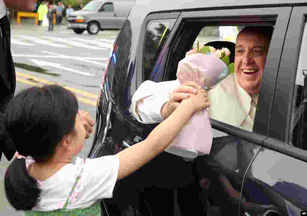 Pope Francis receives a bouquet of flowers from a child as he leaves Seoul at the end of his five-day visit to South Korea, Aug. 18, 2014.