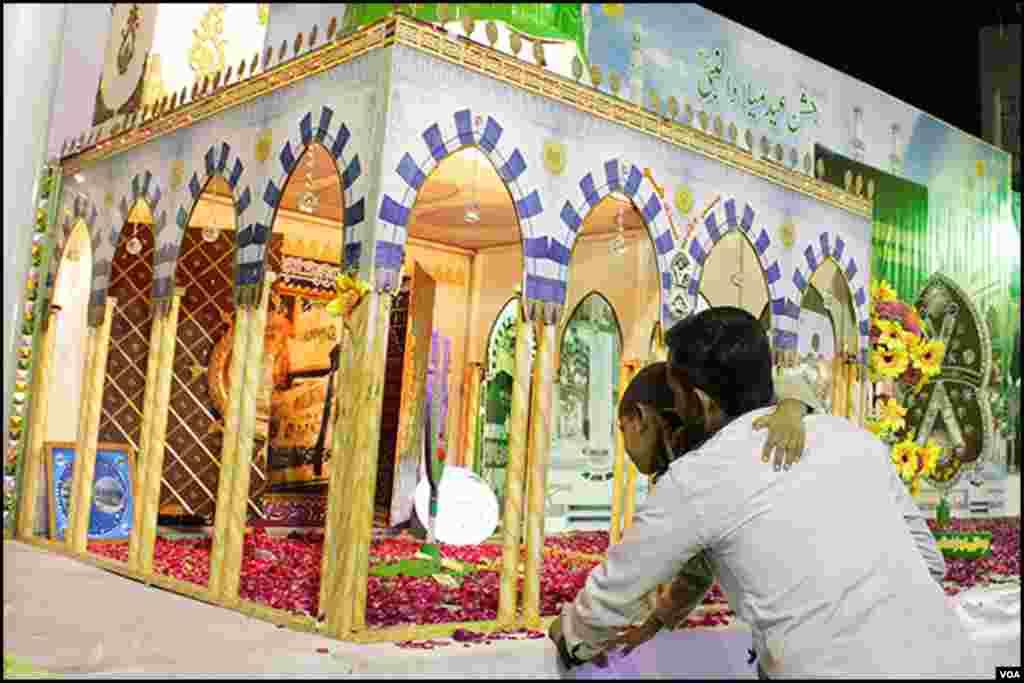 کراچی: ایک شخص عقیدت کے طور پر مدینے کی شبیہ کو چھوتے ہوئے