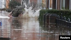 Seorang warga Inggris terjatuh di jalan kota Carlisle yang dilanda banjir, Minggu (6/12).