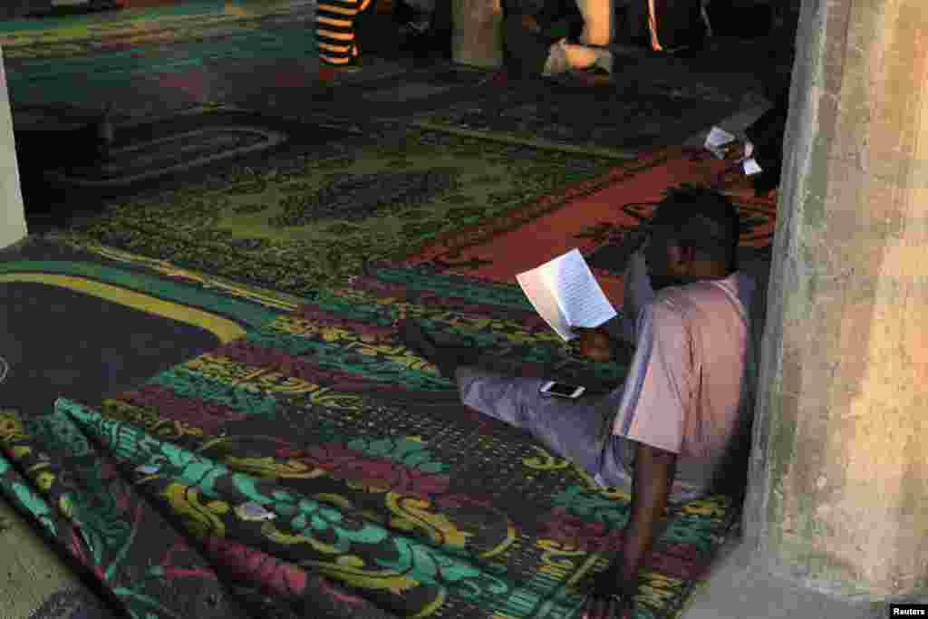 A man reads before breaking fast during the Islamic holy month of Ramadan at Nasfat Mosque in Utako, Abuja.