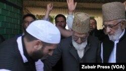 کشمیری لیڈر سید علی شاہ گیلانی پابندیاں اٹھنے کے بعد جمعے کی نماز کی ادائیگی کے لیے گھر سے باہر آ رہے ہیں۔ 30 مارچ 2018