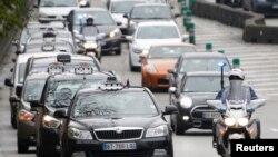 Polisi Perancis berkendaraan sepeda motor, mengawal para penyedia jasa taksi di Paris yang berpawai sebagai protes atas layanan taksi UberPop di kota situ (15/12). Layanan taksi Uber, secara resmi akan dilarang beroperasi di Perancis mulai tanggal 1 Januari 2015.