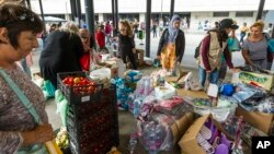 Migrants select among donated goods in the subway in front of Keleti railway station in Budapest, Hungary, Sunday, Sept. 6, 2015.