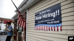 FILE - A sign advertising employment hangs outside a restaurant in Middleton, Massachusetts, July 24, 2017.