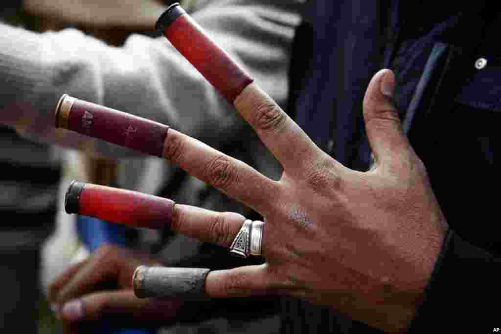 A protester on near Tahrir Square with spent shotgun shells on his fingers. (VOA - Y. Weeks)