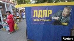 Žena u Sevastopolju prolazi pored preizbornog plakata Liberalno demokratske partije Rusije Vladimira Žirinovskog