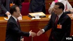 2013年3月5日即将离任的中国总理温家宝在第十二届人大开幕式上和他预计的继任者副总理李克强握手。(美国之音东方拍摄)