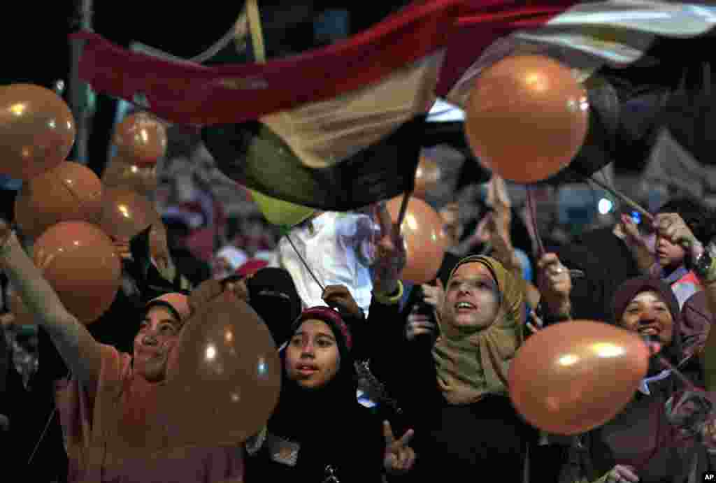 Supporters of Egypt's ousted President Mohamed Morsi hold balloons and national flags as they celebrate the first day of the Eid al-Fitr feast, Cairo, August 8, 2013.