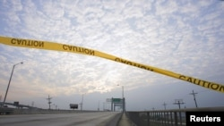 FILE - Caution tape floats in the wind over a walkway running alongside the Danziger Bridge in eastern New Orleans, Louisiana, Nov. 10, 2005.