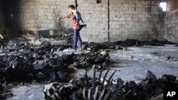 NOTE: GRAPHIC CONTENT - A rebel fighter walks inside a warehouse containing the remains of at least 50 burned bodies in Tripoli, Libya, Sunday, Aug. 28, 2011. A survivor said they were civilians killed by pro-Gadhafi soldiers.