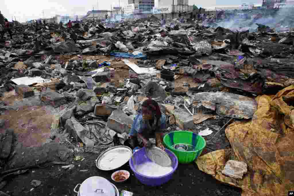 A girl washes the lid of a cooking pot amid the ruins of a market destroyed by city officials in Benin's main city of Cotonou November 17, 2011. Vendors and local residents said police used bulldozers and razed the local market in an effort to tidy the ci