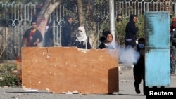 FILE - Students supportive of the Muslim Brotherhood and deposed president Mohamed Morsi clash with riot police in Cairo Dec. 29, 2013.