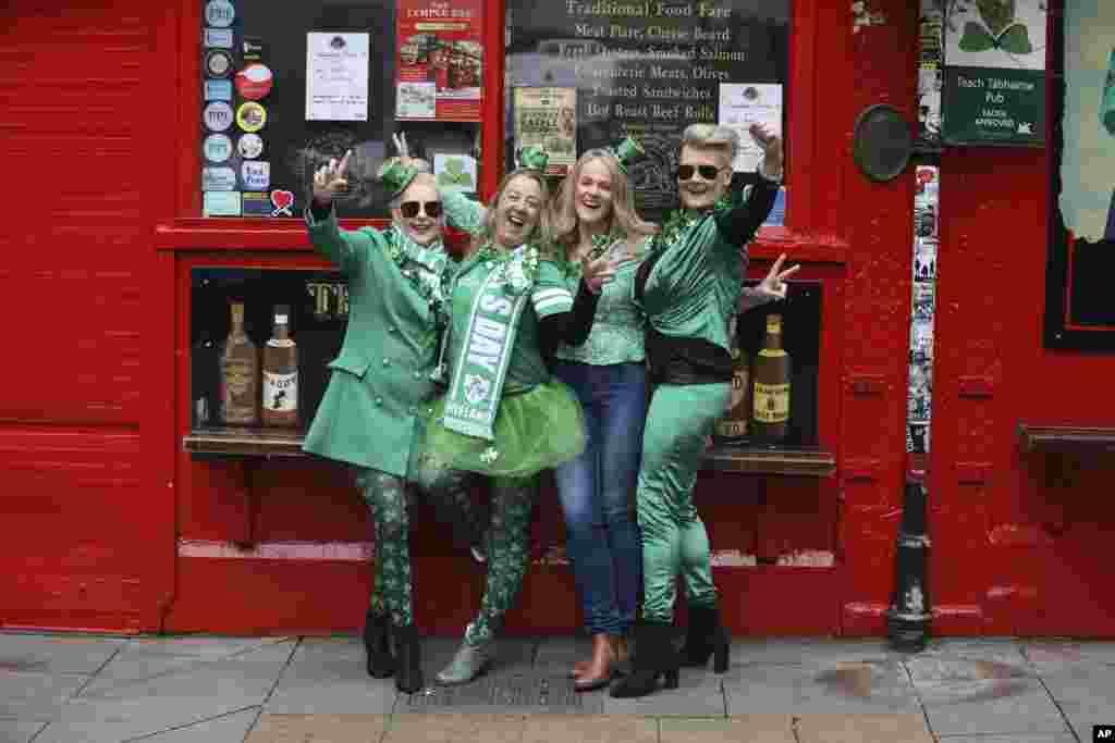 یک گروه گردشگر با لباسهای روز «سنت پاتریک» در مقابل یک میکده تعطیل شده در مرکز شهر دوبلین، ایرلند. این روزاز اعیاد مخصوص و تعطیلات ایرلندیها است و در کشورهایی چون آمریکا نیز جشن گرفته میشود.