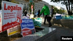 FILE - Pedestrians pass by a cannabis legalization campaign sign in Washington, Nov. 4, 2014.