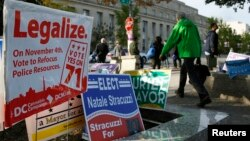 FILE - Pedestrians pass by a DC Cannabis Campaign sign in Washington, Nov. 4, 2014.