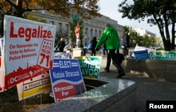 FILE - Pedestrians pass by a D.C. Cannabis Campaign sign in Washington, Nov. 4, 2014.