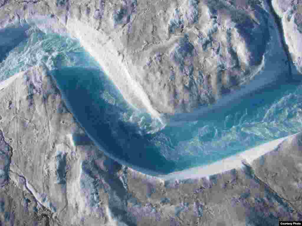The rivers and streams that carry glacial meltwater across Greenland's ice sheet are a beautiful shade of blue, but the water moves so fast and drains so unpredictably into moulins or sinkholes that researchers needed to use a range of high-tech instruments to get their measurements. (UCLA/Laurence C. Smith)