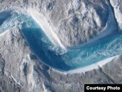 从格陵兰冰盖表面流过的冰川融水景色壮丽,但水流速度极快,而且会难以预测地泻入陷坑,因此科研人员必须用一系列的高科技设备来进行测量。(UCLA/Laurence C. Smith)