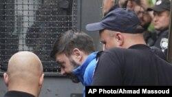 Kirill Vyshinskiy, pimpinan kantor Ukraina di RIA Novosti (kantor berita Rusia) di Ukraina, dikawal dari ruang pengadilan di Kiev, Ukraina, 15 Juli 2019.