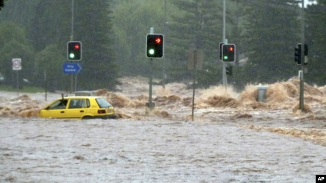 A passenger in a car waves for assistance as a flash flood sweeps across an intersection in Toowoomba, 105 km (65 miles) west of Brisbane, Australia, 10 Jan 2011
