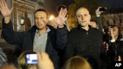 Alexei Navalny, a prominent anti-corruption whistle blower and blogger, left, and opposition leader Sergei Udaltsov, address protesters, Moscow, May 8, 2012.