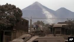 Petugas penyelamat memeriksa rumah-rumah warga yang ditutupi oleh abu vulkanik pasca letusan gunung Volcan de Fuego di Escuintla, Guatemala, Senin (4/6).