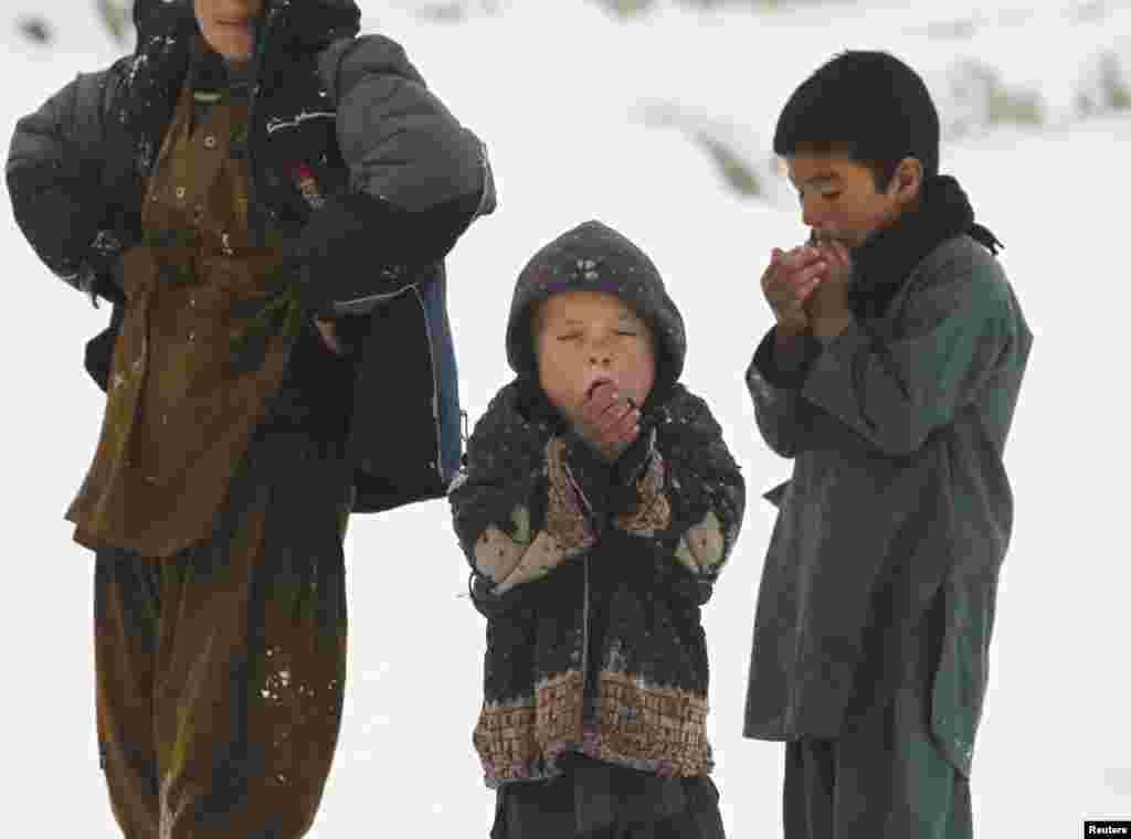 Trẻ em đứng bên ngoài nơi trú ngụ trong thủ đô Kabul, Afghanistan trong một ngày tuyết lạnh giá.