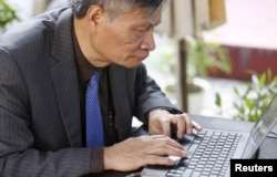 Nguyen Quang A writes a comment on Facebook while sitting at a cafe after an interview in Hanoi, Vietnam, March 1, 2016.