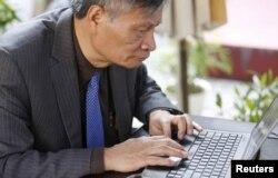 Tiến sĩ Nguyễn Quang A viết một bình luận trên Facebook trong khi ngồi ở quán cà phê sau cuộc phỏng vấn ở Hà Nội, Việt Nam, ngày 1 tháng 3 năm 2016.