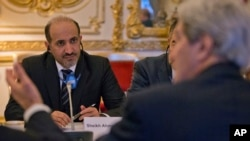 FILE - Syrian National Coalition Chief Ahmad al-Jarba, left, listens to US Secretary of State John Kerry, right, during the start of their meeting at the US Ambassador residence in Paris, France, Monday, Jan. 13, 2014.