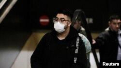 Seorang penumpang mengenakan masker tiba dengan penerbangan langsung dari China di Bandara Tacoma, Seattle, AS, 23 Januari 2020. (Foto: Reuters)