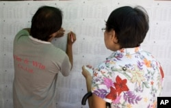 Voters check for their names on a board outside a polling booth in Yangon, Myanmar, Nov. 6, 2015. On Sunday Myanmar will hold what is being viewed as the country's best chance for a free and credible election in a quarter of a century.