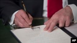 El presidente Trump firma los primeros documentos de su mandato tras ser juramentado en el Capitolio.
