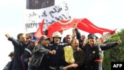 Cảnh sát và nhân viên cứu hỏa Tunisia hô khẩu hiệu trên một chiếc xe cứu hỏa trong một cuộc biểu tình chống đối tại Tunis, ngày 22 tháng 1, 2011