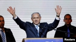 Israeli Prime Minister Benjamin Netanyahu waves to supporters at the party headquarters in Tel Aviv, March 18, 2015.