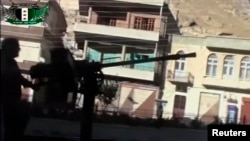 A Syrian rebel fires a heavy machine gun mounted on the back of a vehicle in Maaloula, a suburb of Damascus, in this image taken from video footage obtained from a social media website, September 4, 2013.