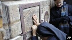Una mujer ora frente a las puertas cerradas de la Iglesia del Santo Sepulcro, lugar donde los cristianos creen que fue el sitio de la crucifixión de Jesús, en Jerusalén, el martes, 27 de febrero de 2018.