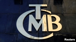 FILE - The logo of Turkey's Central Bank (TCMB) is seen at the entrance of the bank's headquarters in Ankara, Turkey, April 19, 2015.