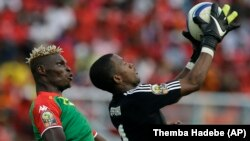 Burkina Faso's Aristide Bance, left, is stopped in the air by Equatorial Guinea's goalkeeper Felipe Ovono, right, Wednesday, Jan. 21, 2015. (AP)