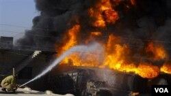 Seorang petugas pemadam kebakaran mencoba memadamkan api setelah terjadi lagi serangan terhadap truk yang mengangkut perbekalan pasukan NATO hari ini.